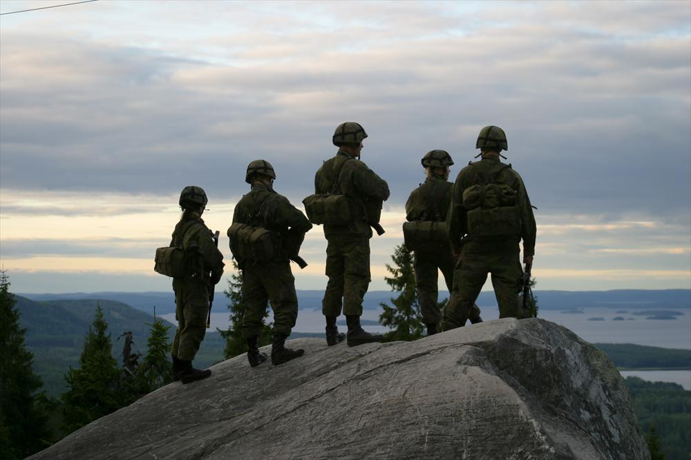 Four conscripts stand on a cliff with a view down to a lake