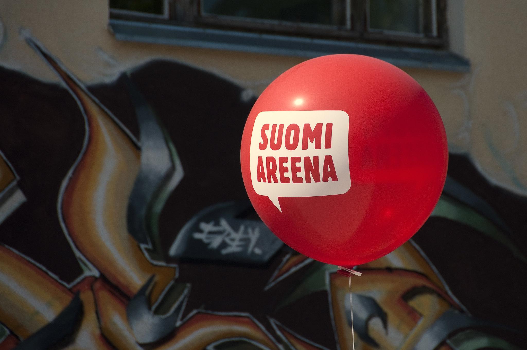 Punainen SuomiAreena -ilmapallo, tummaa taustaa vasten.