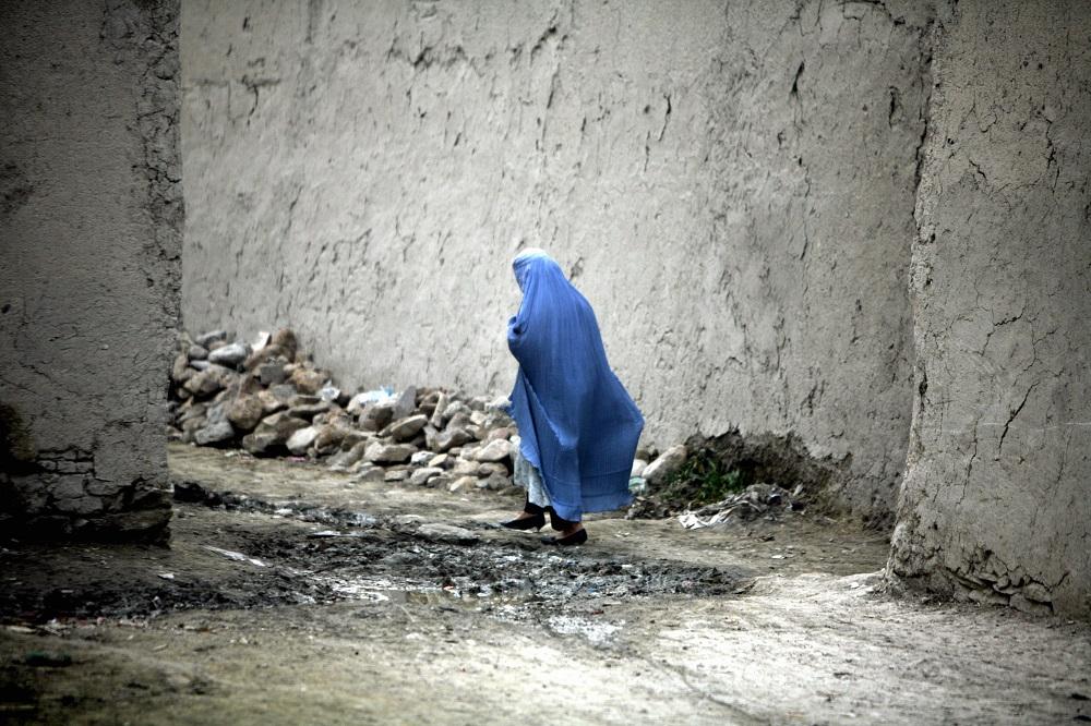 Siniseen kaapuun pukeutunut henkilö kulkee korkeiden seinien välissä.