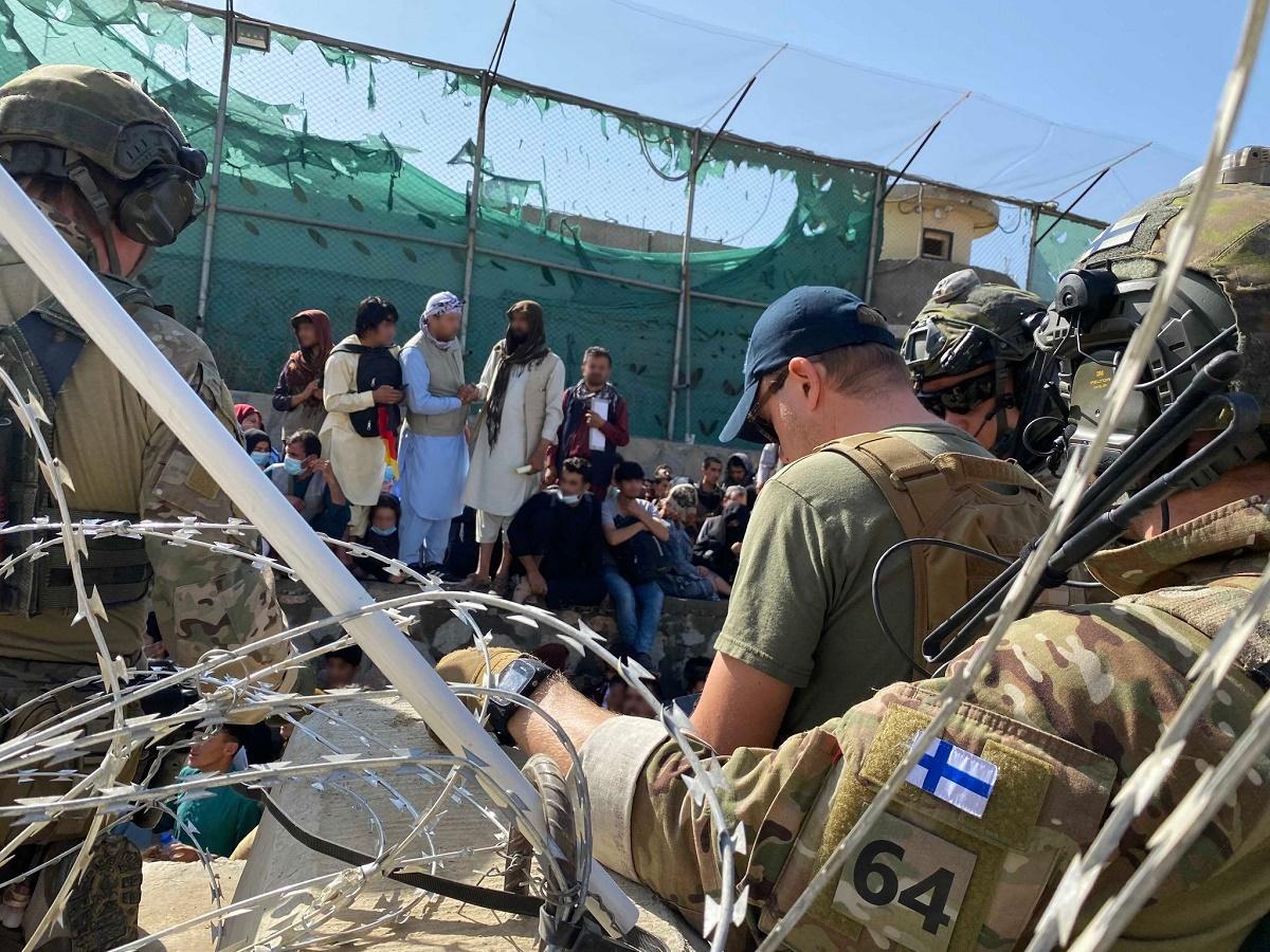 Kabulin kentän kaaosta. Kuvassa suomalaisia sotilaita ja avustustiimin jäseniä ja afganistanilaisia.
