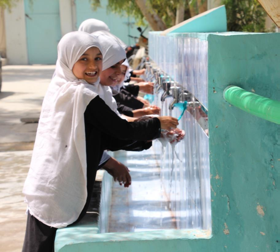 Girls washing their hands under a tap.