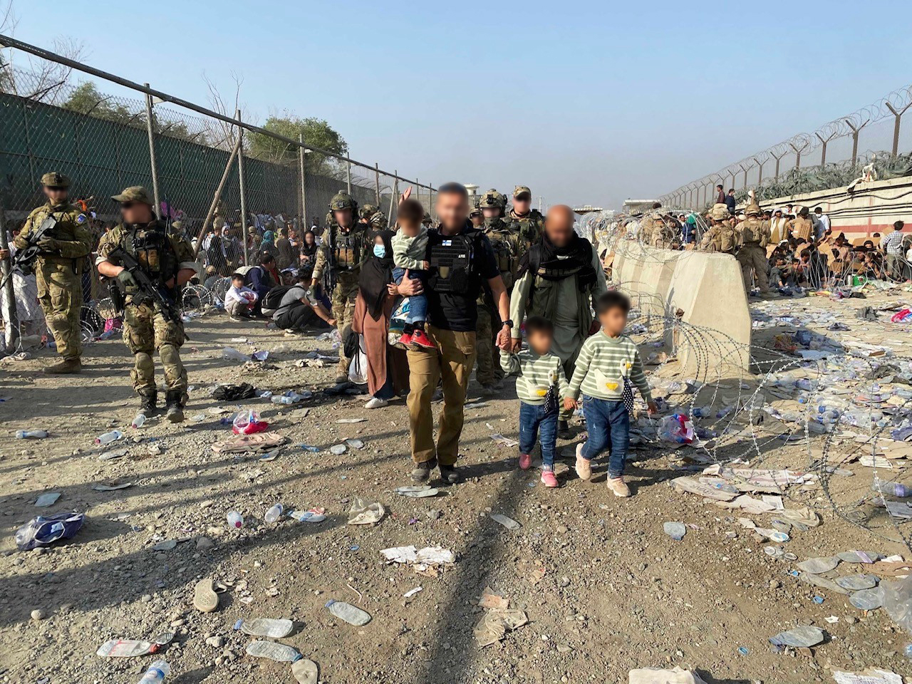 Kuva Kabulin kentokentän läheisyydesta. Suomen avustustiimin jäsen taluttaa kahta afgaanilasta (kasvot tunnistamattomaksi muokatut) . Kuvassa myös Suomen suojausjoukon jäseniä sekä taustalla paljon paikallisia ihmisiä.