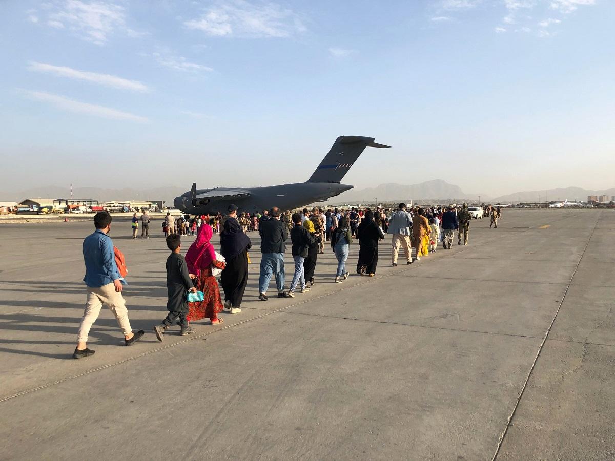 Ihmisiä kävelemässä koneeseen KAbulin kentällä.