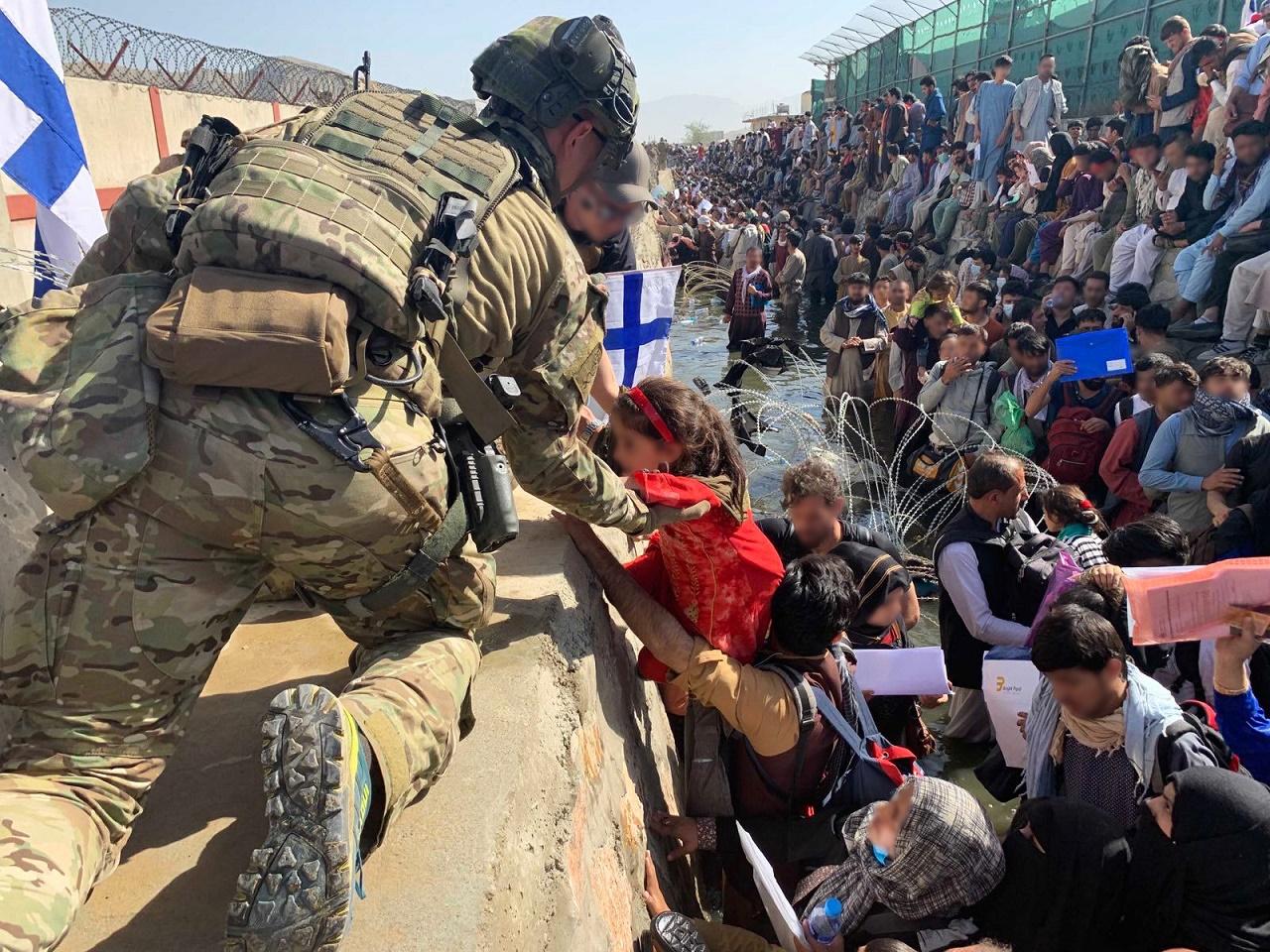 Kuvassa suomalainen suojausjoukon jäsen auttaa pientä afgaanityttöä muurin yli suojaan. Taustalla väkijoukkoa ja kaaosta Kabulin kentän läheisyydessä.