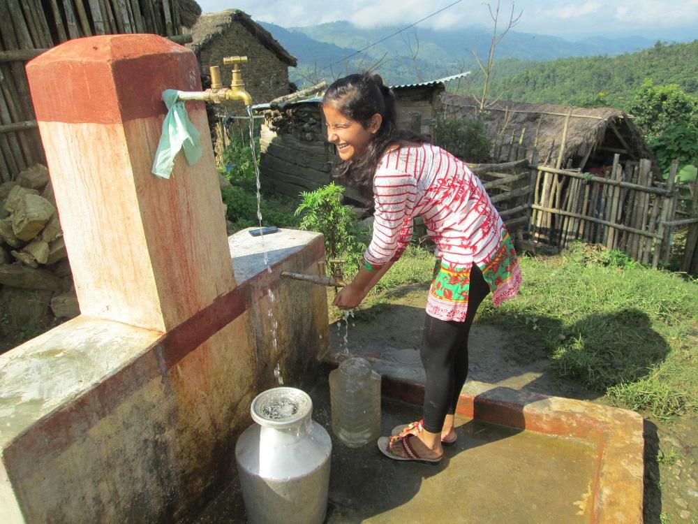 Vatten rinner från kran till flickans händer.