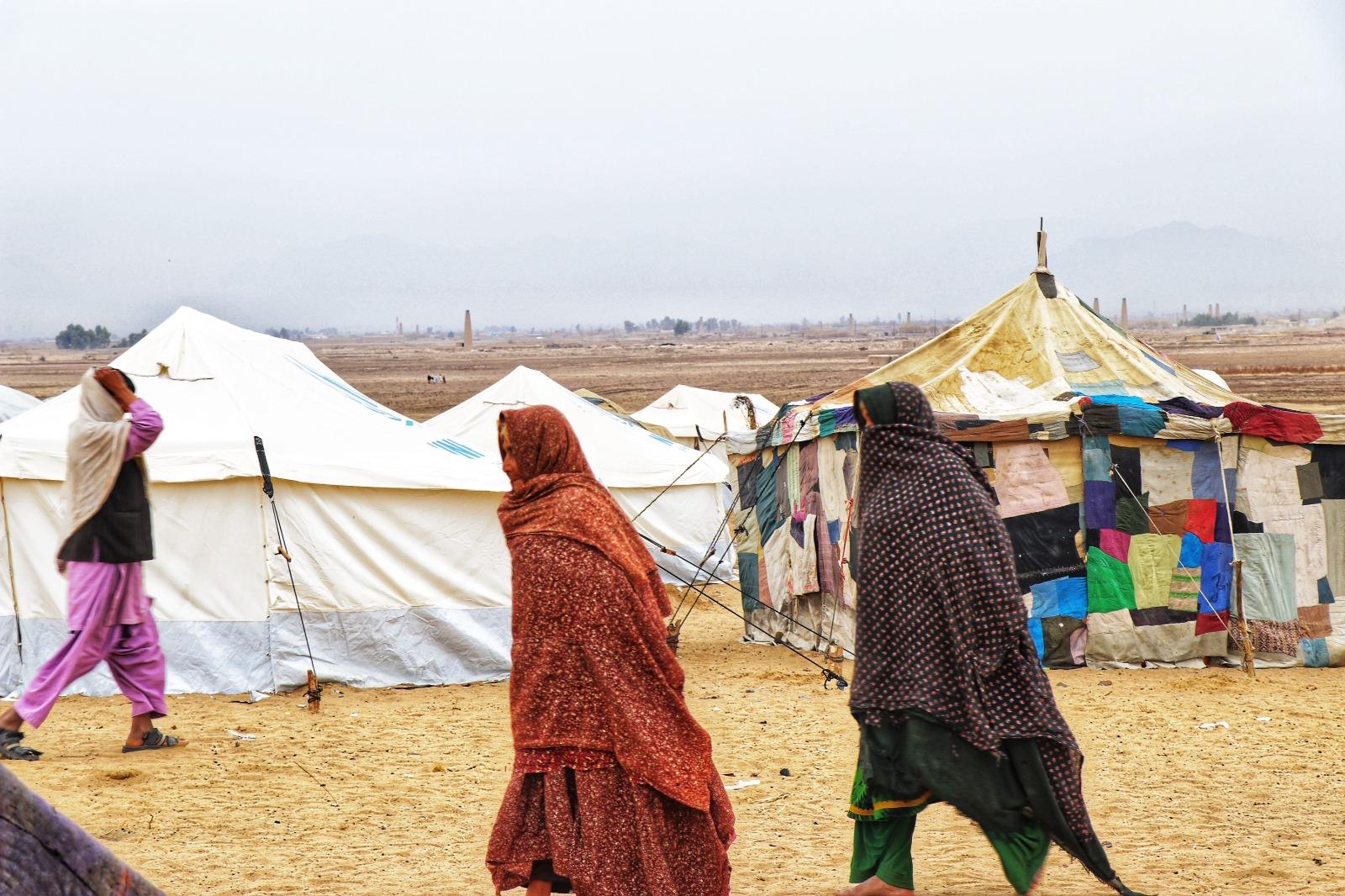 Två personer går, de bär långa dukar omkring sig, i bakgrunden telt.