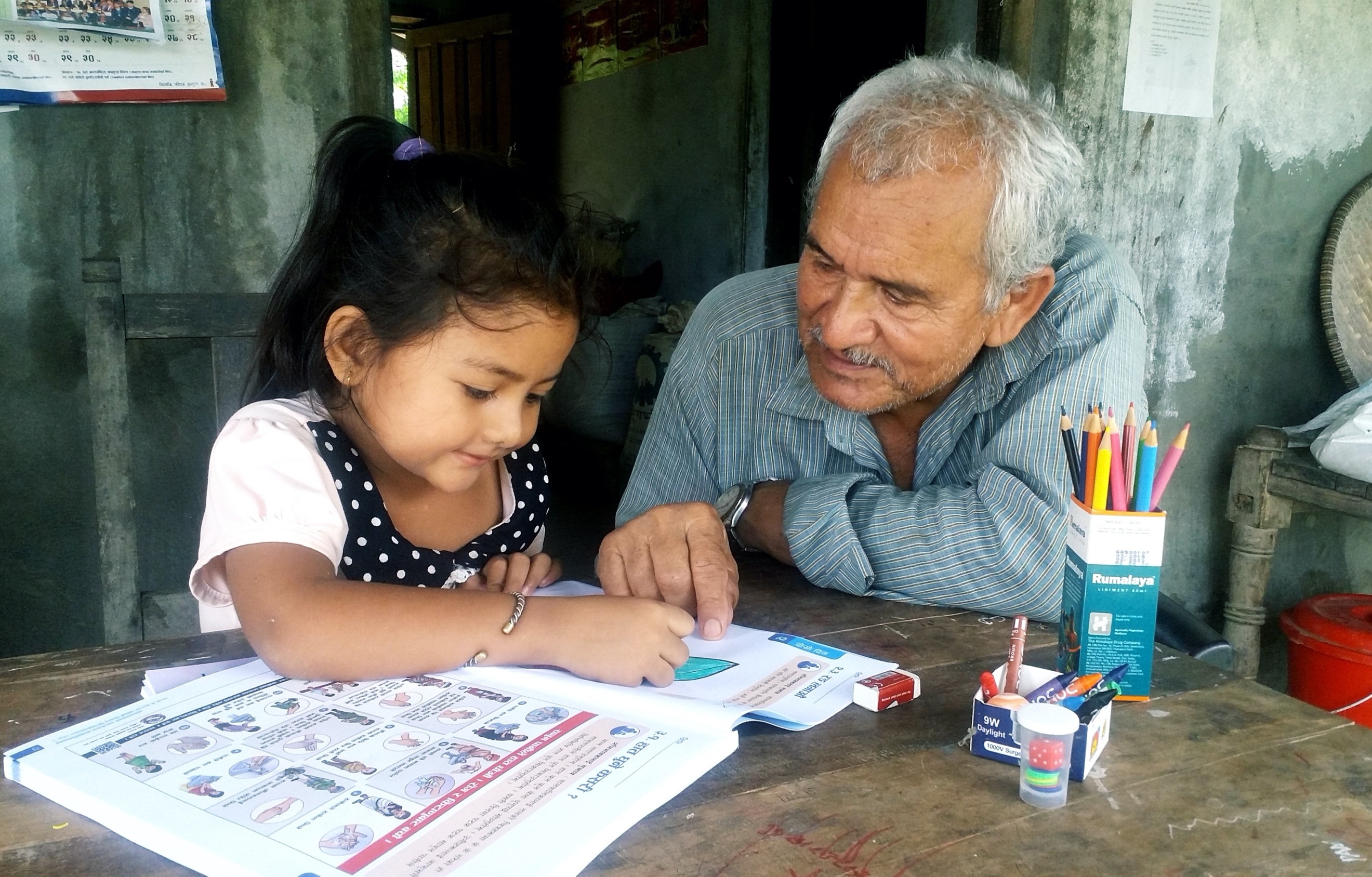 Subechha Puri, 5, does lessons with her grandfather Nandalal in their home in Kapilvastu District in western Nepal. To help the little girl continue learning at home, the family has been making use of a self-learning pack.