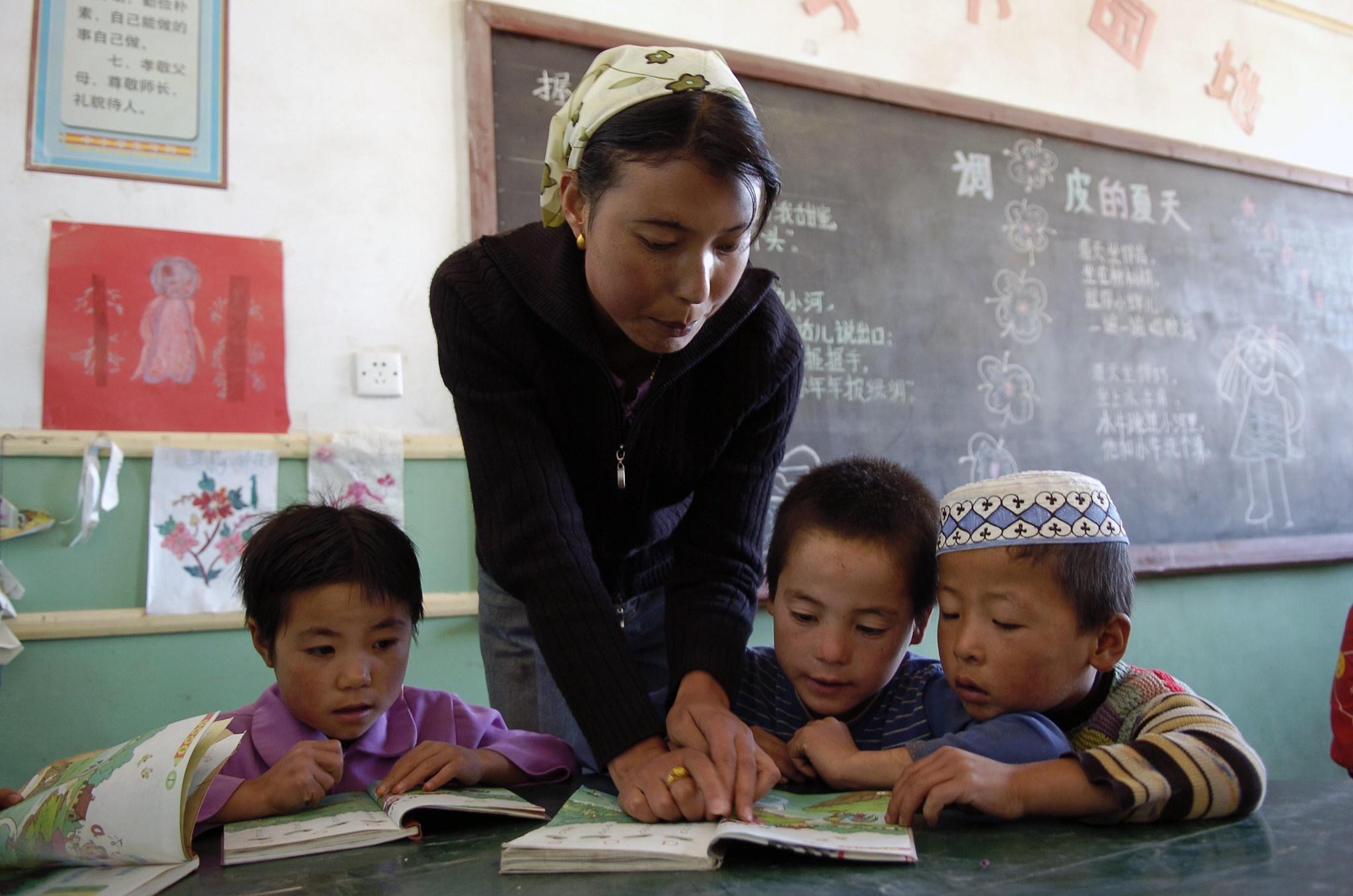 Nainen kumartuneena kirjaa kohti kahden lapsen välissä. Kolmas lapsi tutki omaa kirjaansa. Taustalla liitutaulu.