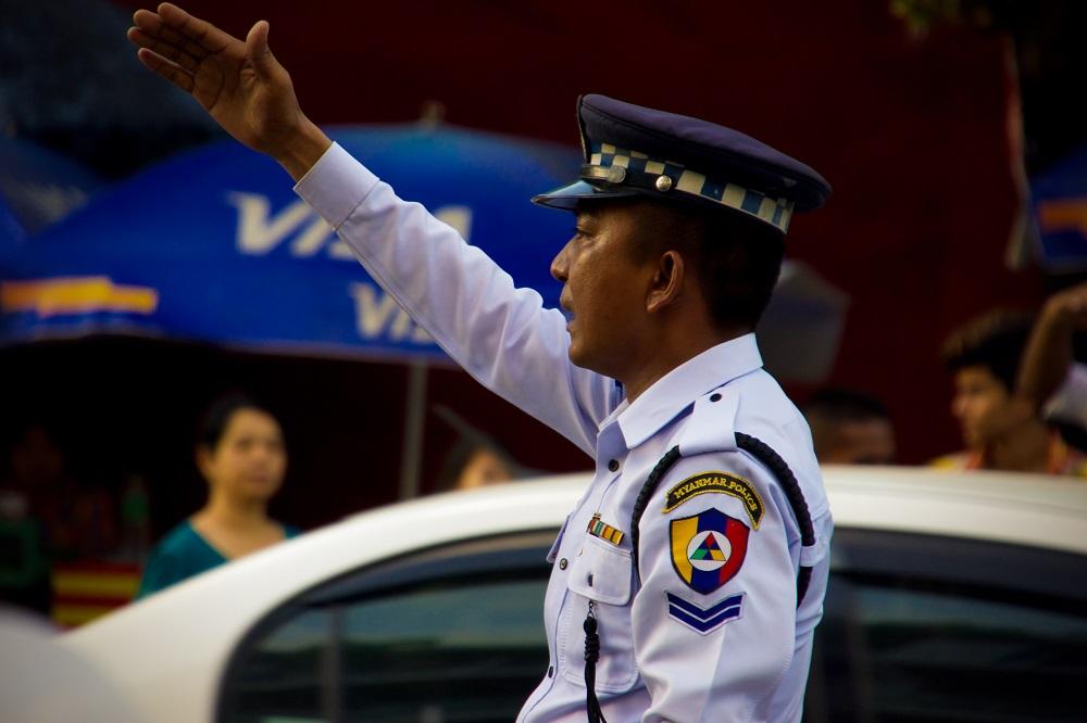 En polisman har sin hand up.