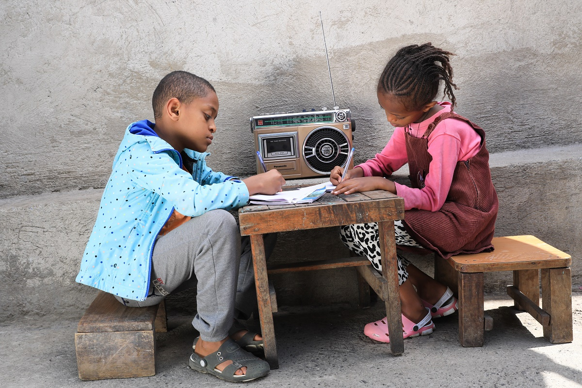 Two Ethiopian children sitting by a table, listening to radio and writing in a notebook.