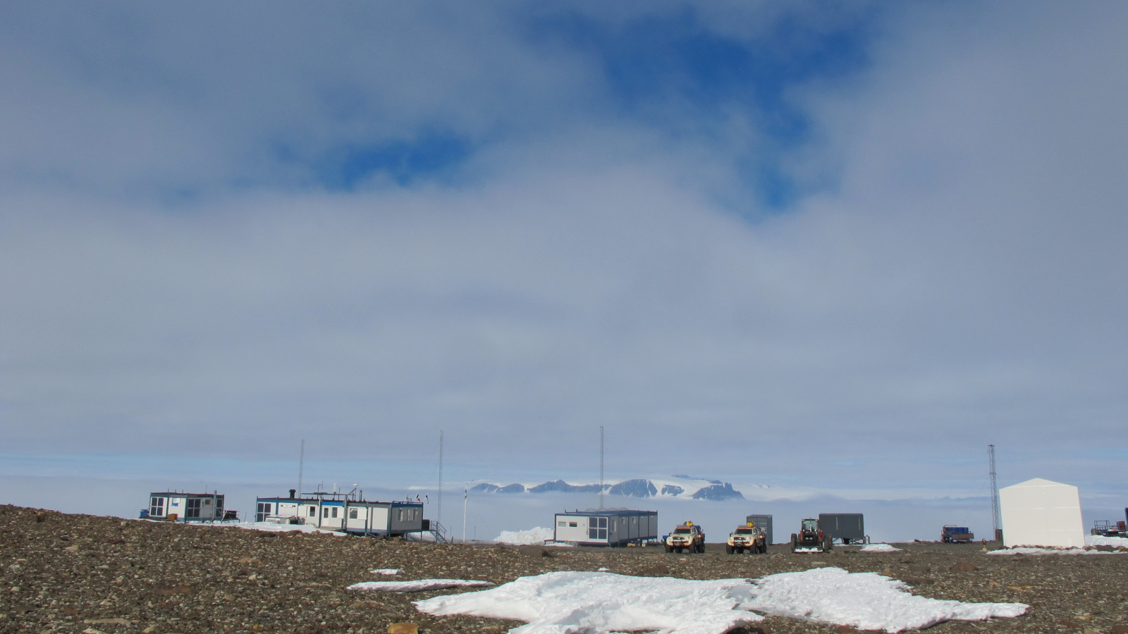 Containers and vehicles in an antarctic landsscape.