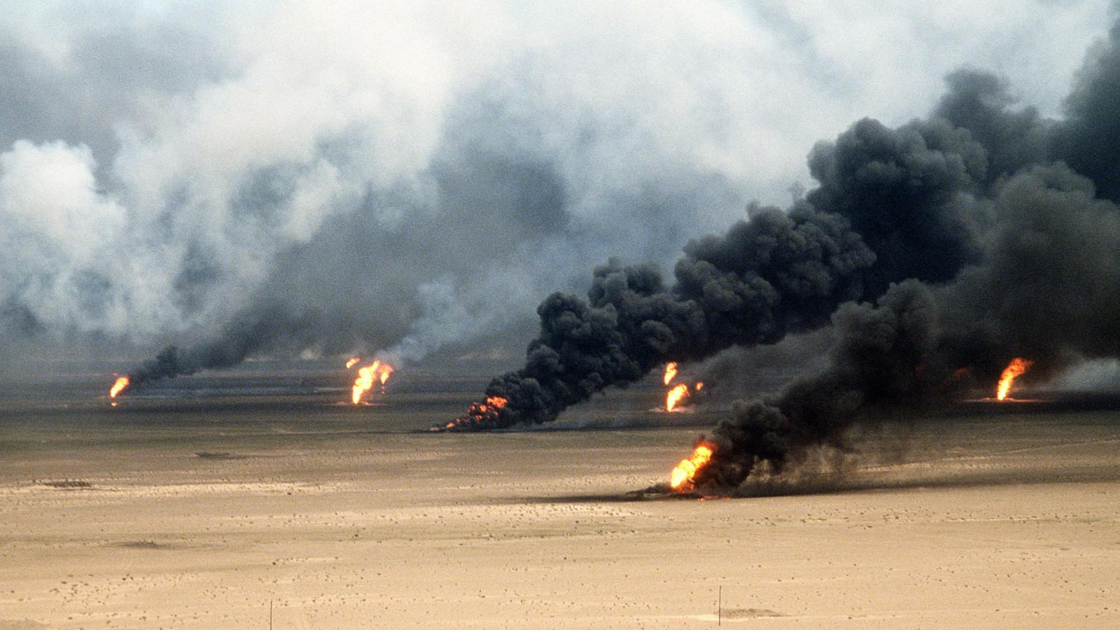 Mustina savuttavia öljypaloja hiekka-aavikolla.