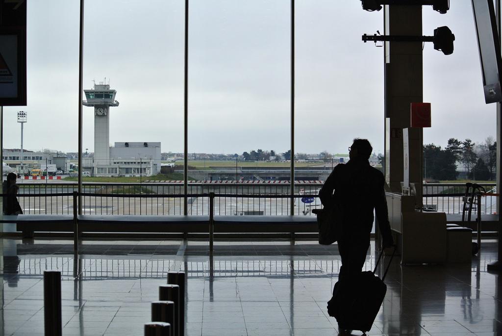 Matkustaja ja pieni perästä vedettävä matkalaukku lentoasemalle